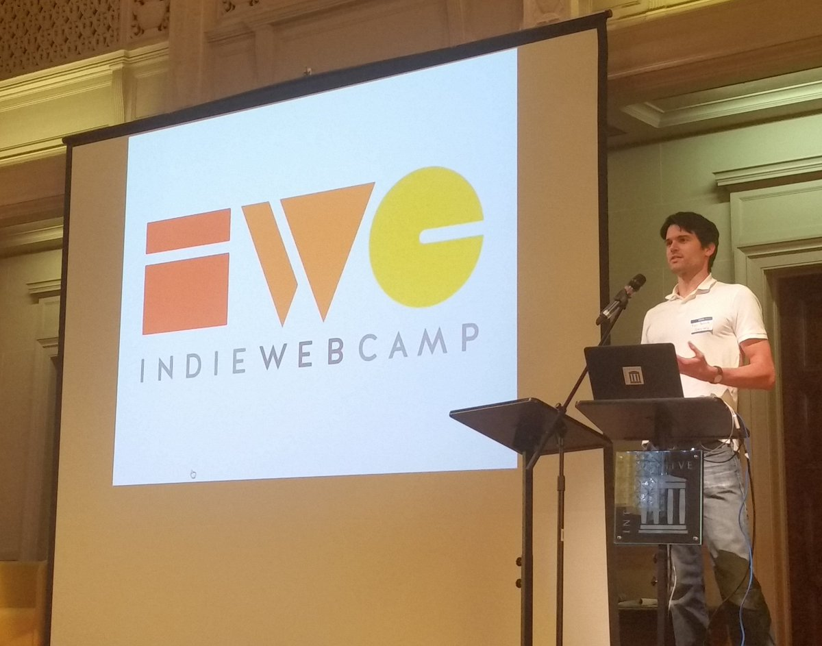 Photo of IndieWebCamp lightning talk opening slide and Ryan Barrett presenting