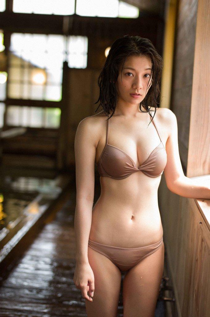 ベージュの水着で立つ佐藤美希
