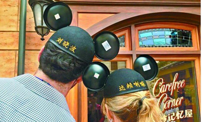 昨日上海迪士尼開幕,免費讓顧客在米奇老鼠帽上繡字。兩名《洛杉磯時報》(Los Angeles Times)的記者入園採訪時,特別在園區裏戴上繡上劉曉波、達賴喇嘛等簡體字的米奇老鼠帽,在樂園「美妙記憶屋」門前合照。 https://t.co/wCi7R4aqd5