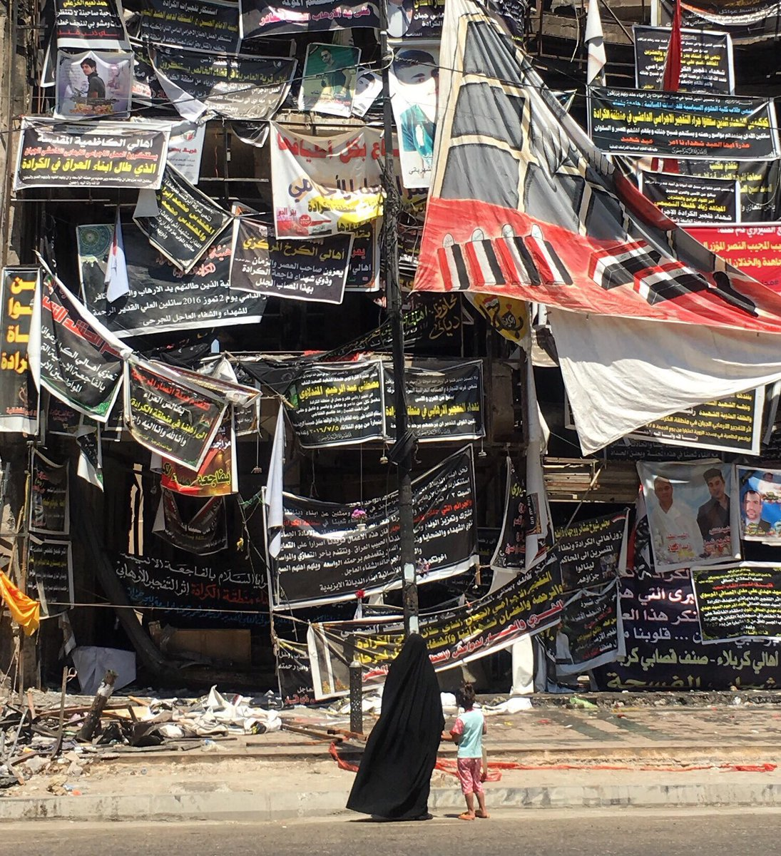 Woman & child look at banners bearing names of some of 323 people killed by blast in Iraq capital 1 month ago today.