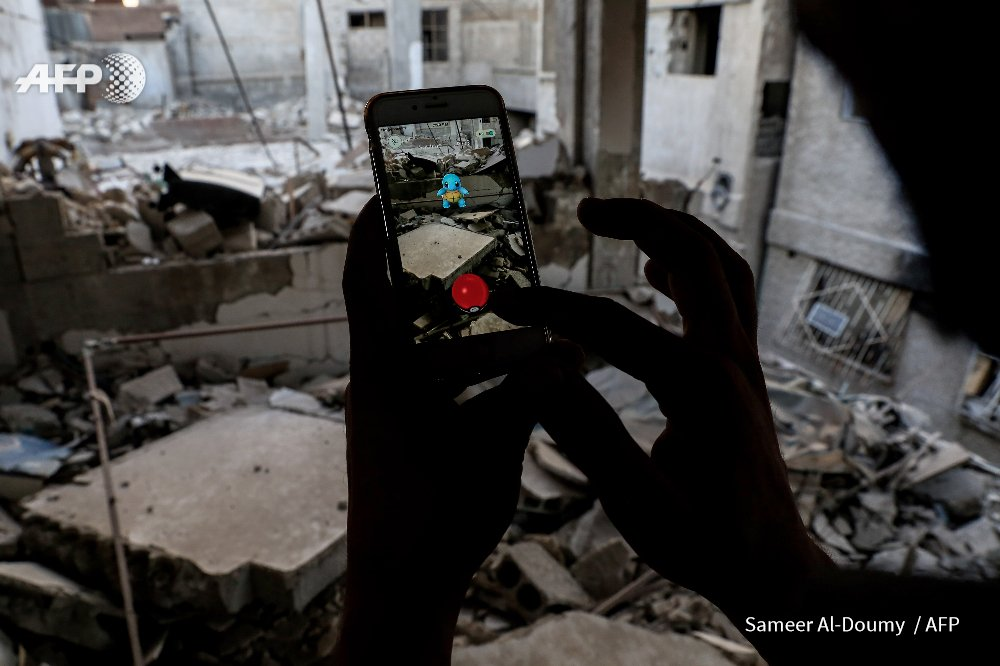 A gamer uses Pokemon Go application on mobile to catch a Pokemon amidst rubble in Douma, Syria