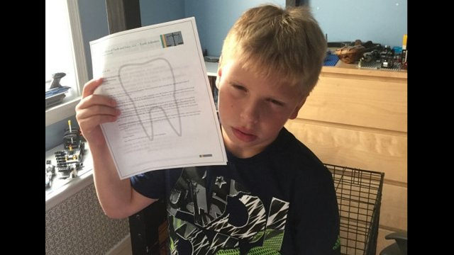Young boy gets a chore list from the Tooth Fairy under his pillow