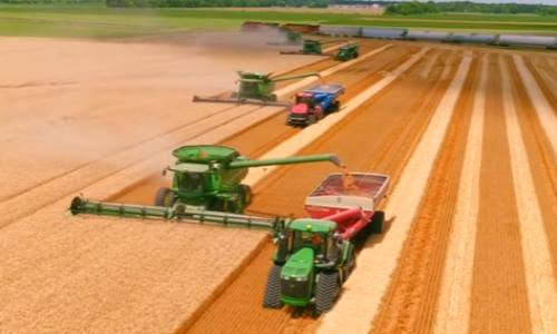 Agricultural tractor plows soil and plantings of agricultural cultures,  blurred background, filmed on telephoto