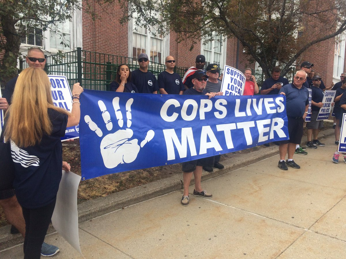 Off duty police officers from across eastern MA protesting BlackLivesMatter banner on Somerville city hall.