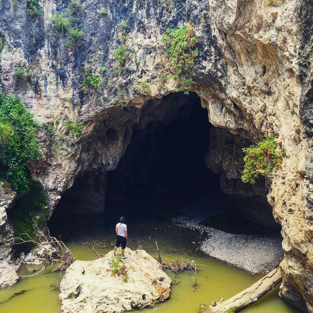 Visitante admirando la enorme cueva de Puente de Dios
