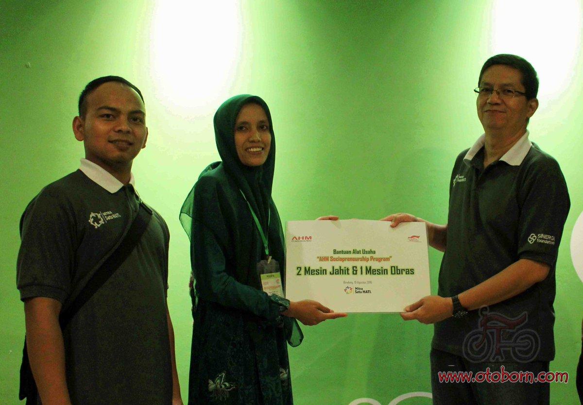 CSR Manager AHM Yudi Yozardi (kanan) menyerahkan bantuan berupa mesin jahit dan mesin obras kepada UKM Mitra Satu Hati konveksi asal Subang, Jawa Barat disela-sela acara training sociopreneur Mitra Satu Hati di Hotel Fave Hyper Square Bandung Jawa Barat (19/8).
