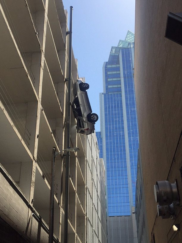 There's a car hanging from a parking garage between 5th & 6th in downtown Austin. Don't worry, no one is inside. https://t.co/ebuStz7nRT