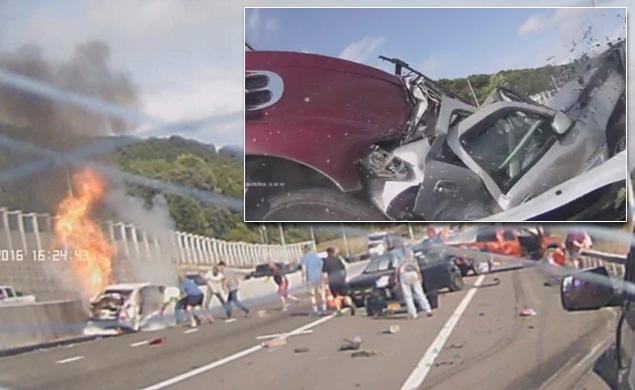 shows a woman pulled out of her burning vehicle following crash with a tractor-trailer