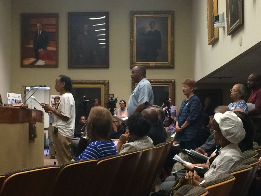 Resident protests begin in water bill increase hearing.