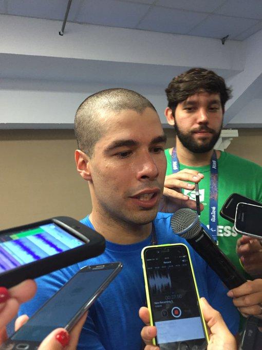 Daniel Dias concede entrevista a jornalistas na zona mista do Estádio Aquático. Repórteres apontam celulares para gravar o que ele fala.