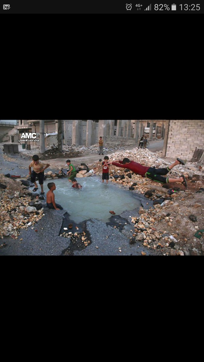 How kids play in Aleppo. Kids swim in a water hole created by a missile strike #Syria https://t.co/warFw7yqZI