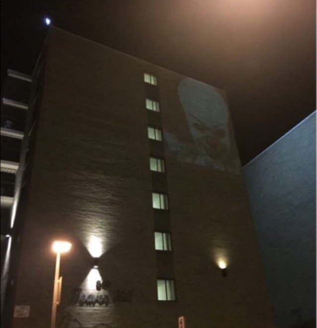 An image of a clown is being projected on the side of Beaver Hill apartments https://t.co/Px2QG4YOaw
