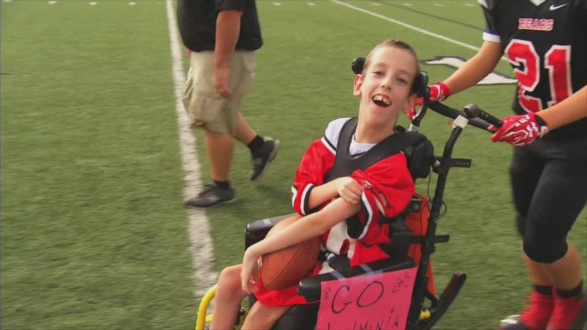 Rival teams help boy with cerebral palsy score touchdown in honor of late father