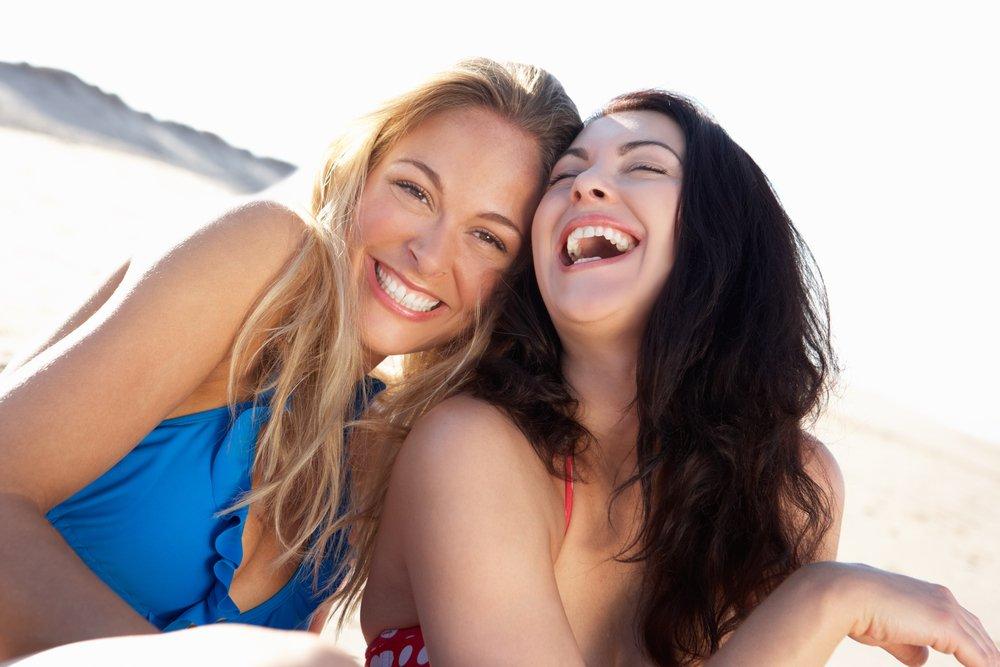 Cheerful Girls Enjoying Hot Drinks And Chatting