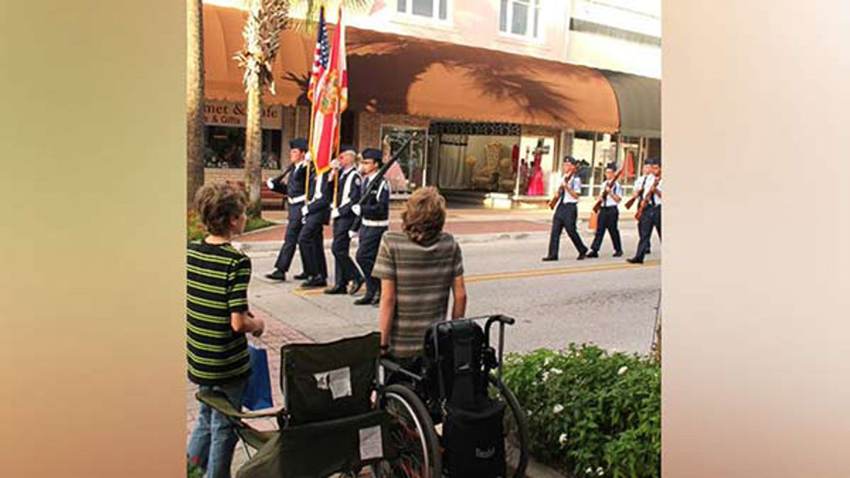 Teen with spina bifida stands up from wheelchair to honor American flag