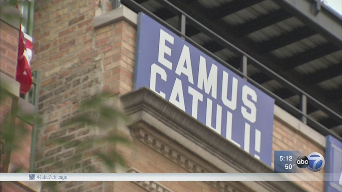 What is the meaning of Eamus Catuli sign hanging outside Wrigley Field?