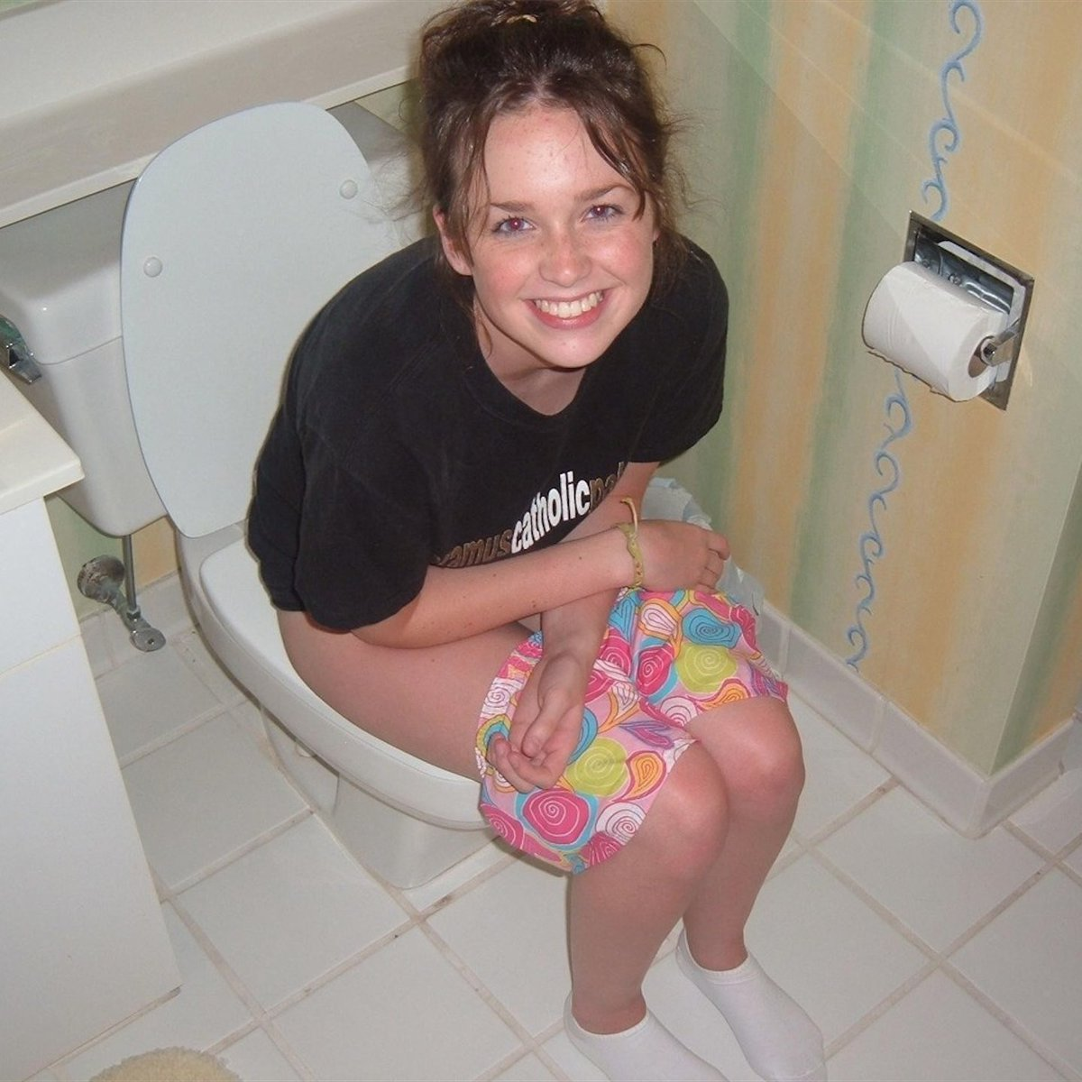 Blond girl peeing seated on a toilet stock photo