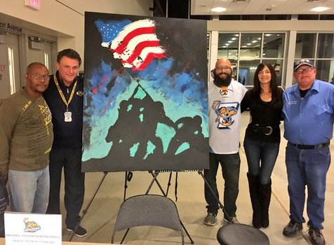 Artist paints canvas while singing national anthem during hockey game