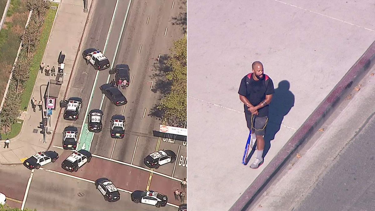 Man holding baseball bat pacing sidewalk outside Hall of Justice in DTLA; deputies on scene