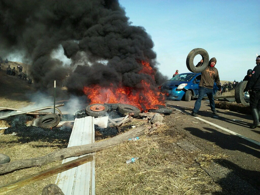 Happening now: #NoDAPL water protectors blockading highway 1806 with cars, tires & fire amid fears 100+ police about to raid resistance camp