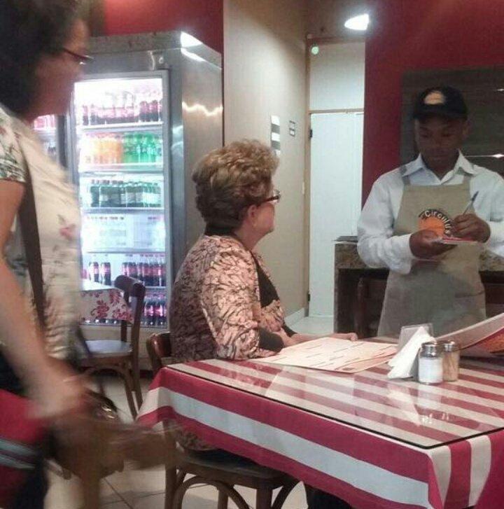Foto tirada por frequentador do Circulus Lanches. Dilma sentada em uma mesa da lanchonete fazendo um pedido, em meio a todos os outros clientes.