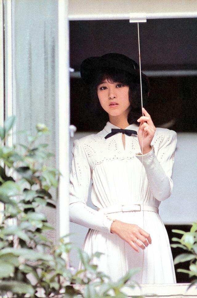 黒い帽子に白いドレスを着て外を見つめる松田聖子