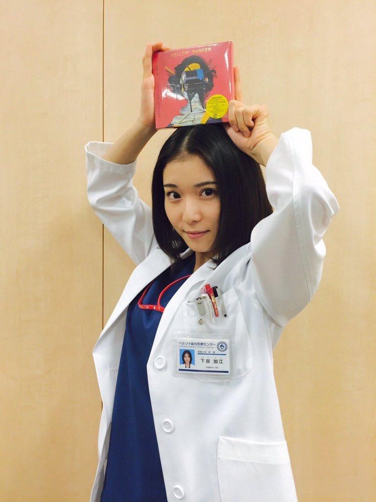 女医の格好をして頭の上にCDを持つ松岡茉優