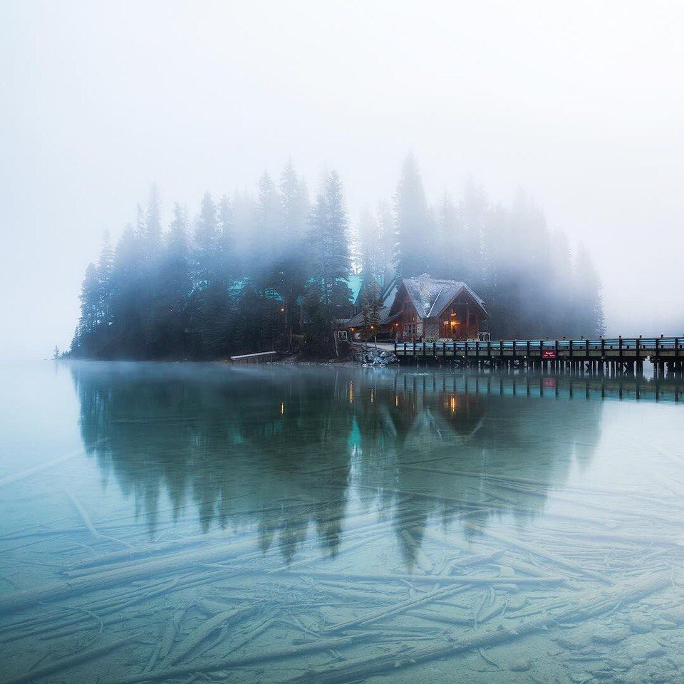 Enveloped in mist cottage on the shores of Lake Emerald. Canada.