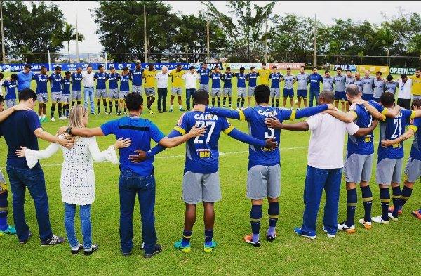 Jogadores, comissão técnica, funcionários do Cruzeiro e imprensa reunidos no centro do campo de treinamento em oração pela @ChapecoenseReal.