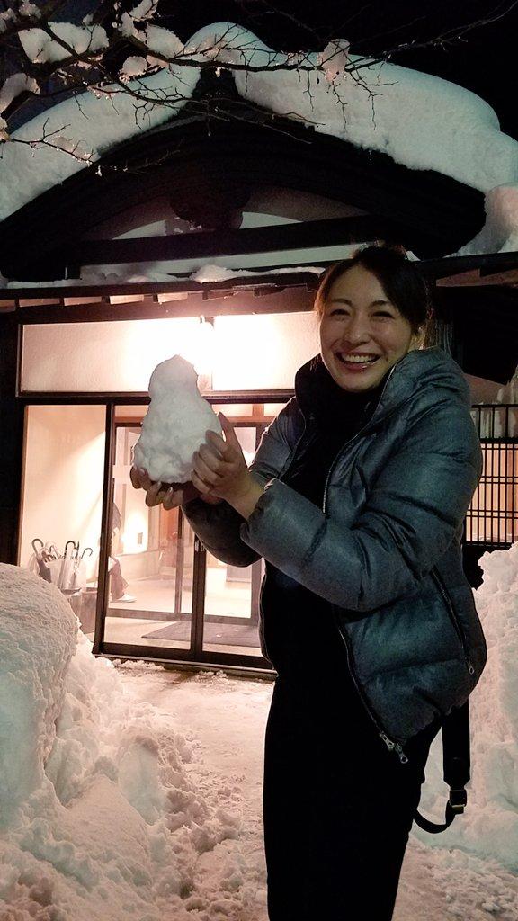雪の積もった家の前で雪だるまを手に持って笑顔の小椋久美子