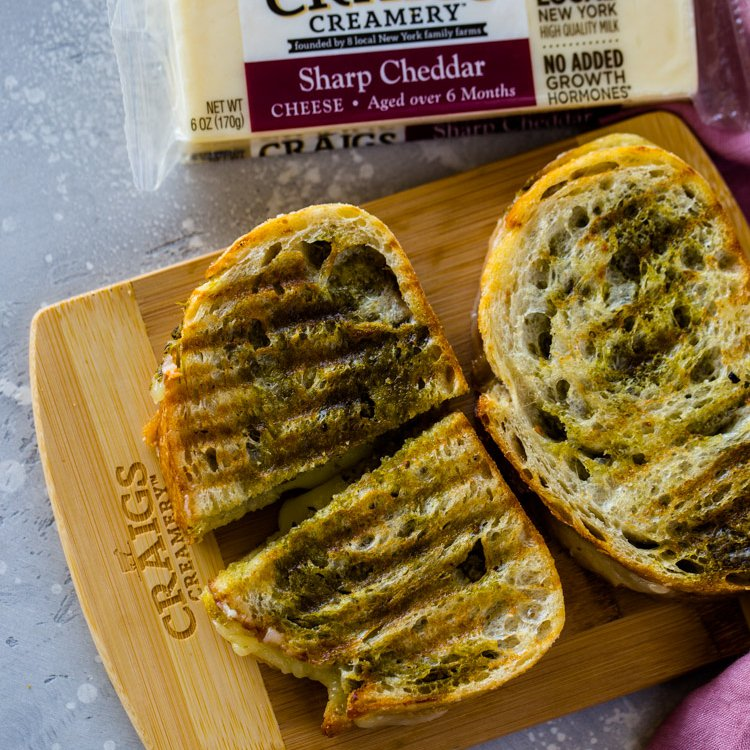 Pesto and cheddar grilled cheese paninis featuring Craigs Creamery are super easy to make and extremely delicious! Get the recipe and learn about my new favorite cheese brand that is working to fight food waste!