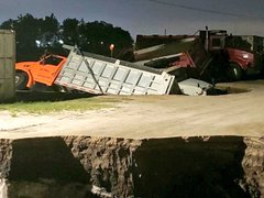 Dump truck swallowed by hole in the road.