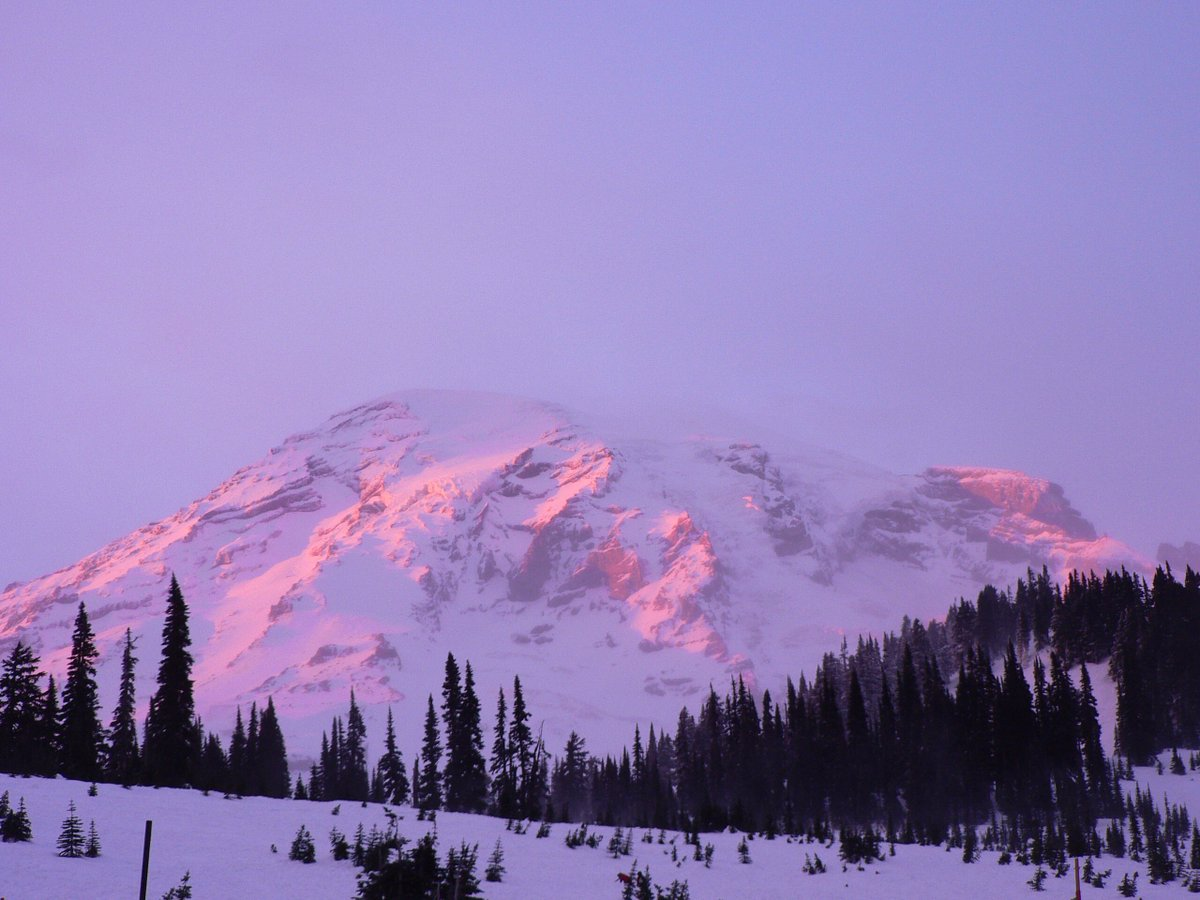 9a99df693ec68b An alpine glow creates a purple hue on a mountain.