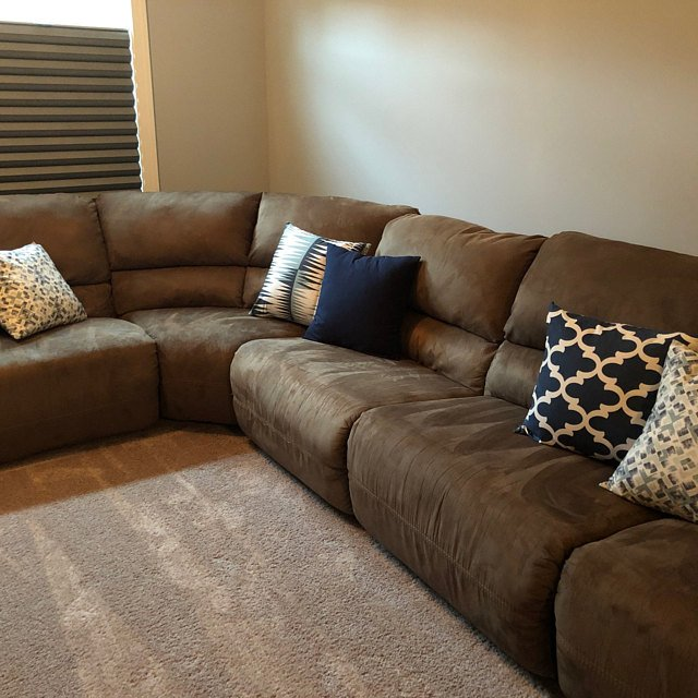 A brown couch with a collection of pillows in blue and brown geometric prints.