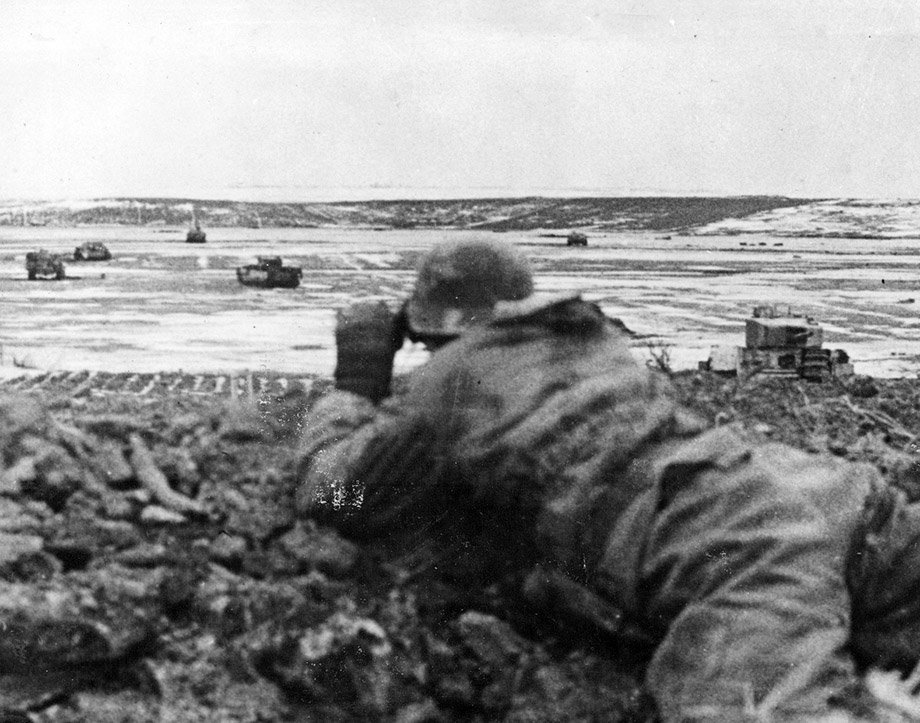 A German soldier observes the battlefield which is littered with several knocked-out Soviet vehicles, including lend-lease British Churchill tanks.   Pskov Oblast, Russia, March 1944. #WW2<br>http://pic.twitter.com/EOD9j0JxXW