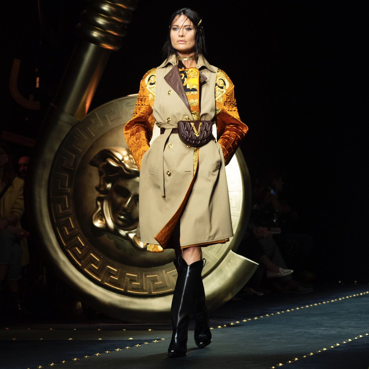 Shalom Harlow opens the #VersaceFW19 runway show wearing a trench coat with Barocco print accents, a Virtus belt bag and knee high V-Western boots. #MFW  Watch the show:  https://t.co/drIKwcAARG