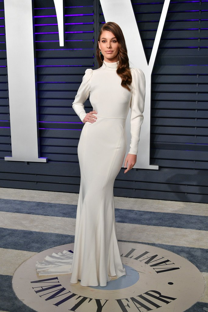 f0ccdb0aa87 Camila Morrone wore a  MoniqueLhuillier Spring 2019 Bridal high-neck sheath  gown with a draped bodice and a signature open back to the 2019 Vanity Fair  ...