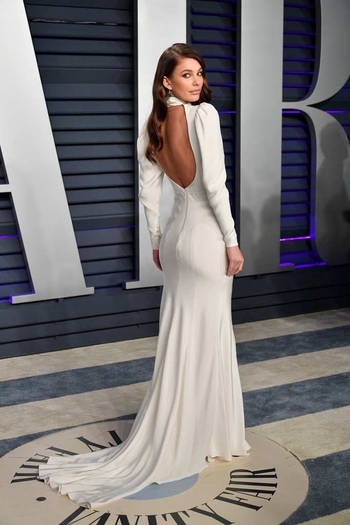 95dd417fcf19 Camila Morrone wore a  MoniqueLhuillier Spring 2019 Bridal high-neck sheath  gown with a draped bodice and a signature open back to the 2019 Vanity Fair  ...