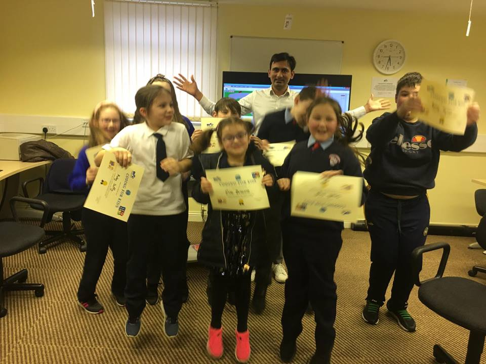 A group of excited kids jump up in the air holding their coding certs