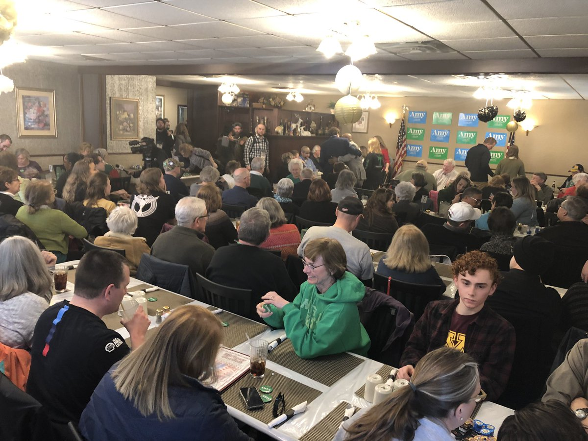 Packed restaurant in Davenport for @amyklobuchar. The attendees' St. Patrick's-themed green outfits and scarfs match Klobuchar's Wellstone-themed green grassroots campaign color #IACaucus