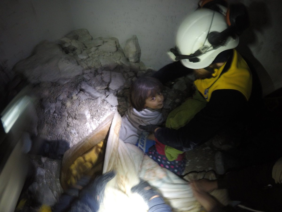 Image showing a girl pulled out alive from under the rubble on an aerial attack of Syrian government forces on Saraqeb city in Idlib suburbs, at dawn of Mar 7.