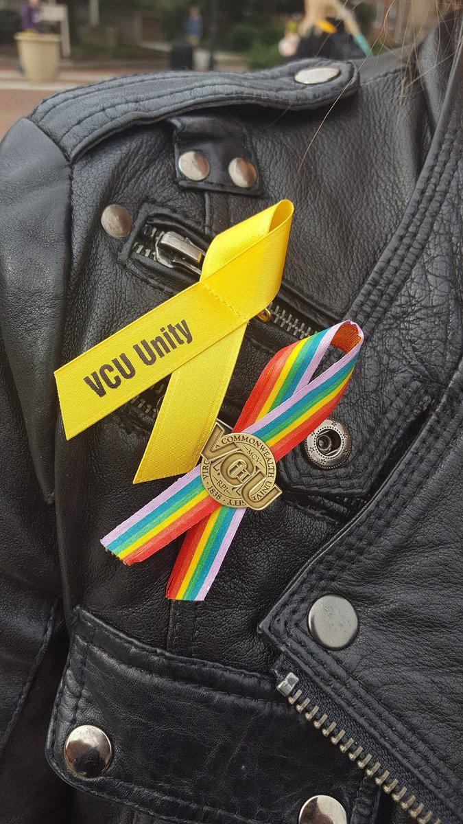 a7a55c23ea Close up photo of two ribbons on a black leather jacket. One is yellow  reading