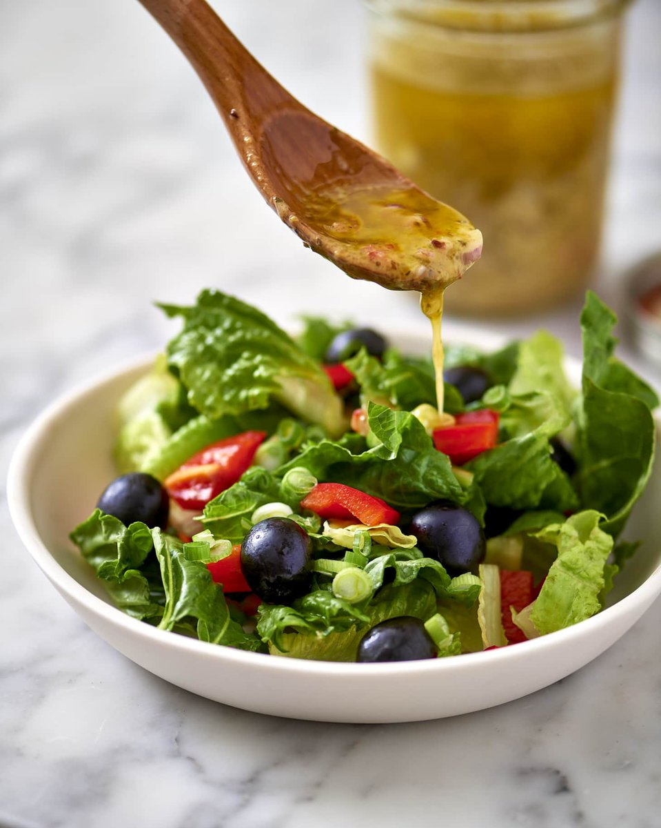 A wooden spoon drizzling dressing into a bowl of salad