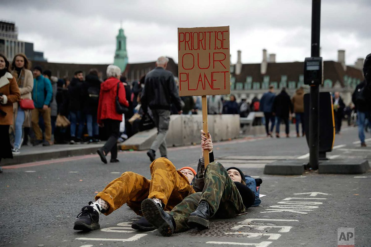 Youngsters lie down as they take part in a student climate protest at the bottom of Westminster Bridge, today in London. @Matt_Dunham