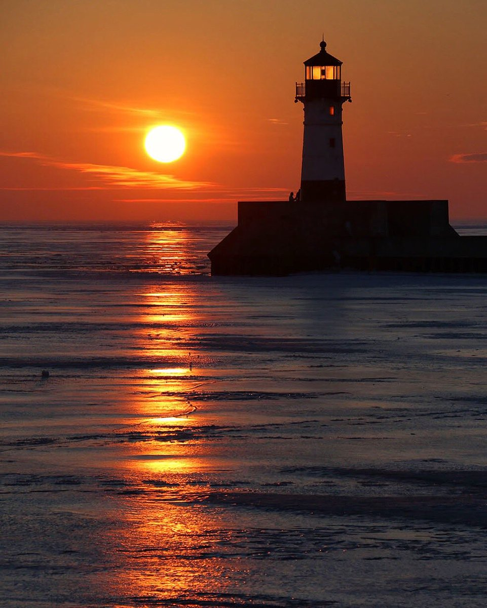 This morning's sunrise over the ice of Lake Superior and the #Duluth North Pier Lighthouse, as seen from the shore in Canal Park <br>http://pic.twitter.com/6pjX1QrFoX