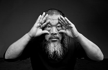 A black-and-white portrait of a bearded Asian man (Ai Weiwei), who is looking directly at the camera, and holding his own eyes wide open.