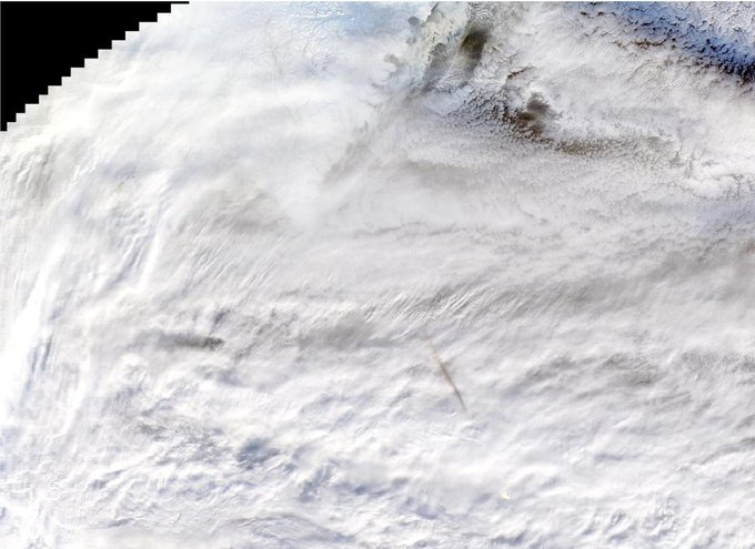 Satellite image of a meteor's shadow, visible as a gray streak in the lower center, above white clouds