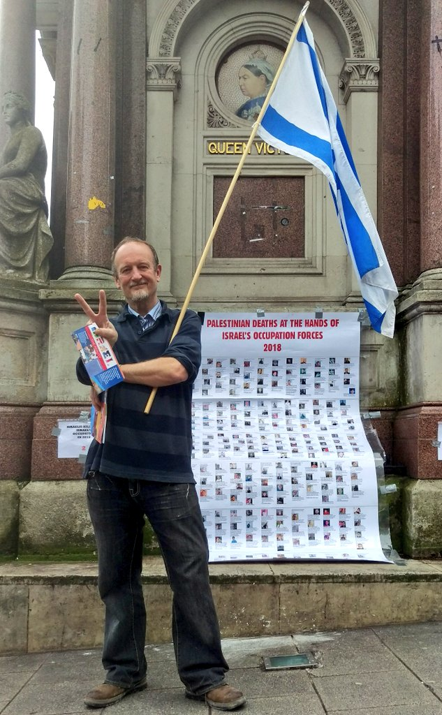"Supporter of @SussexFriends of Israel deliberately and ""proudly"" standing in front of poster of Palestinians killed by Israel"