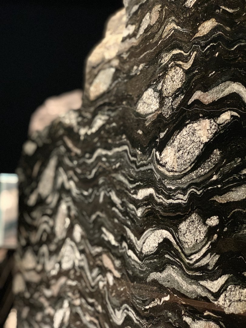 When rocks are compressed, they deform by bending & folding. When a conglomerate is subjected to high temp & pressure, the pebbles within it can be flattened, rotated, & squeezed into long, thin lines—such as with this rock specimen from the Hemlo greenstone belt in Ontario.