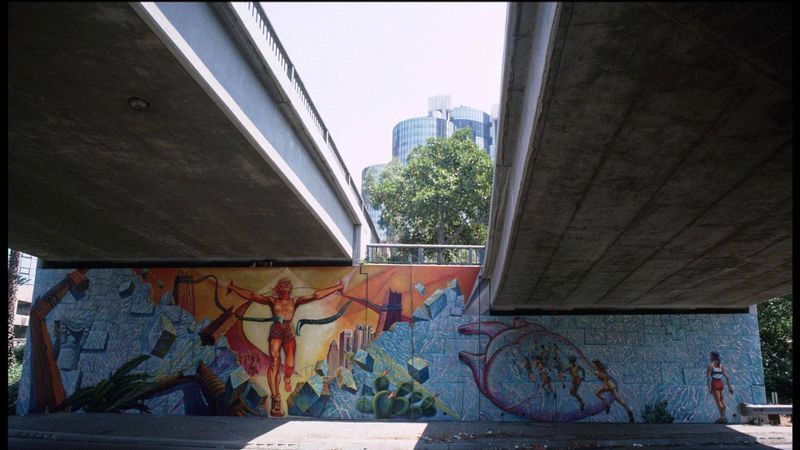 """The mural, titled """"Hitting the Wall,"""" was painted on the 110 Freeway near the 4th Street exit in downtown Los Angeles to commemorate the first time women were allowed to run in an Olympic marathon at the 1984 Summer Games in L.A."""